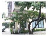 Tampak samping bangunan dengan halaman dan pepohonan